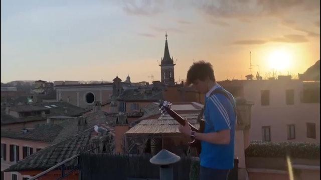 Roman musician plays guitar from rooftop overlooking spectacular Piazza Navona