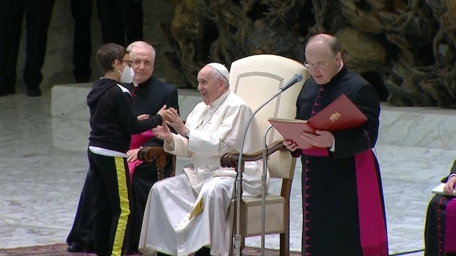 Child spontaneously climbs on stage to ask Pope Francis for his cap