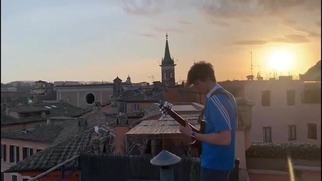 Roman musician plays guitar from rooftop overlooking spectacular Piazza Navona