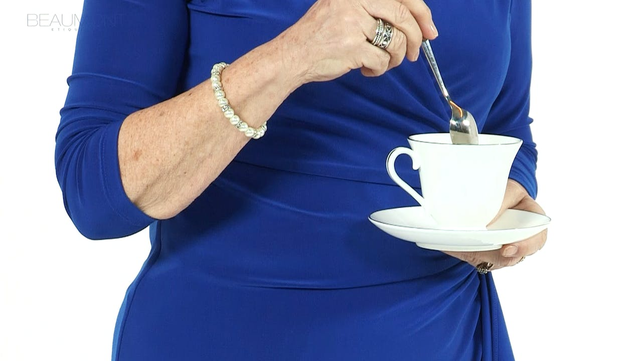 Holding a teacup and stirring your tea